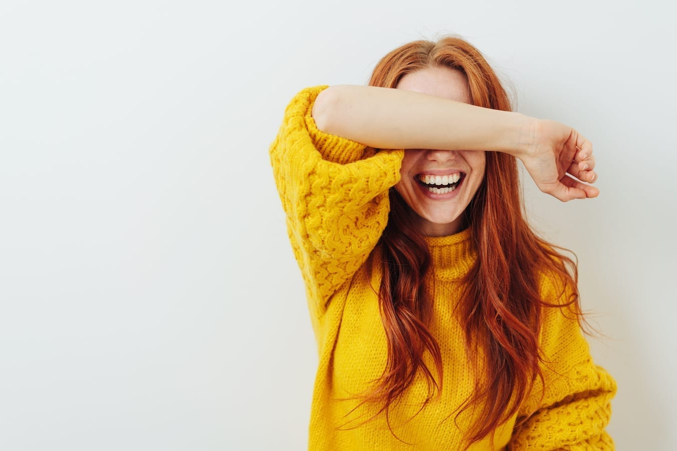photo d'une femme avec sn avant bras sur les yeux. Souriante