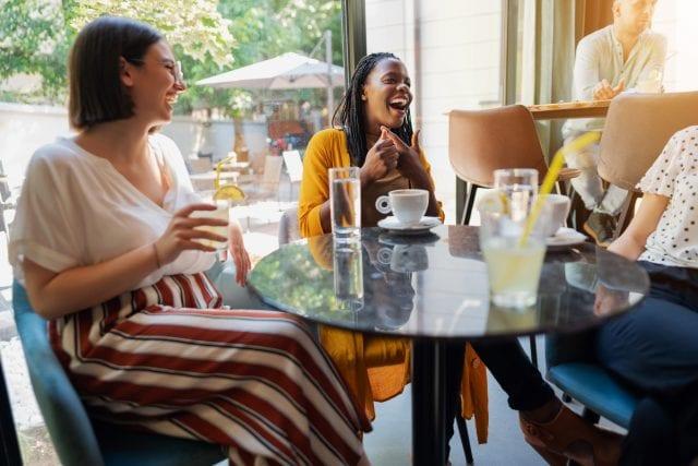 Photo de femme qui rient autour d'une table de café